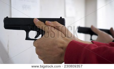 Instructor Teaches A Man To Handle A Weapon Or Gun. Close Up Of Male Hands With Gun While Training W