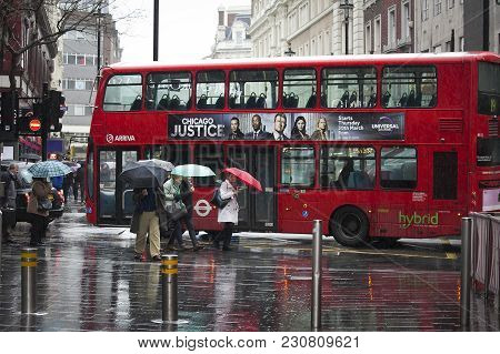 London, England - March 12, 2017 Tourists With Umbrella Walking Against A Background Of Double-decke