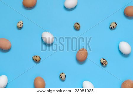 Hen White And Brown Eggs And Quail Eggs On Blue Background, Copy Space. Healthy Food Concept. Top Vi