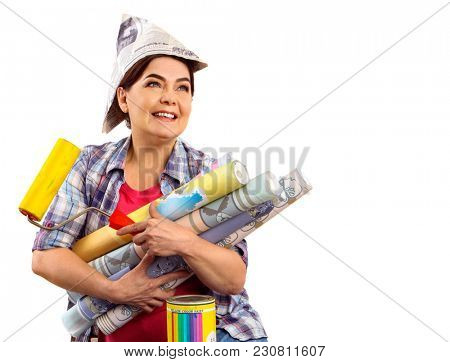 Repair home elderly woman holding paint roller for wallpaper. Senior woman in newspaper cap renovation apartment. Woman is happy to move new apartment. Loan for housing for pensioners.