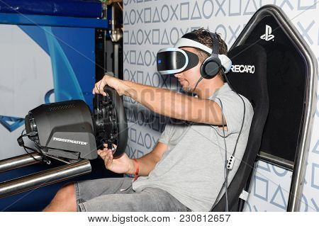 Cologne, Germany - August 24, 2017: A Trade Fair Visitor Is Playing A Racing Game With Vr Headeset A