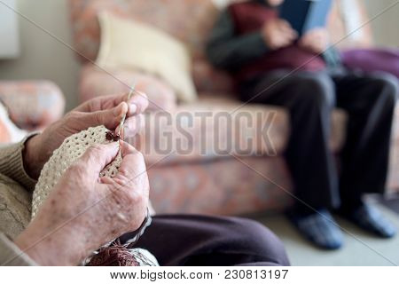 closeup of an old caucasian woman crocheting a piece with a beige thread and an old man reading a book sitting on a couch in the background