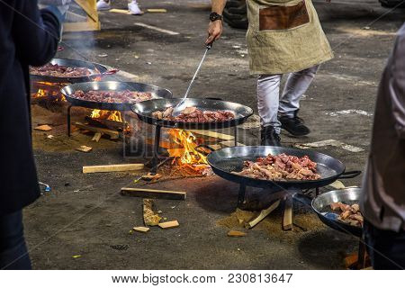 Valencia, Spain - 3/12/2018:  Row Of Paella Pans With Meat Cooking Over An Open Fire To Feed The Cre