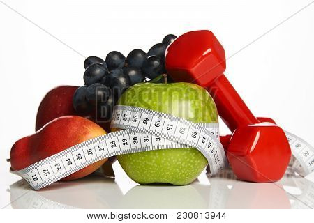Fitness Equipment And Healthy Food Isolated On White. Red Dumbbells With Fresh Fruit And Green Apple