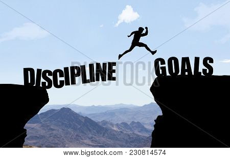 Man Reaching Hand To Woman Jumping Over Abyss In Front Of Mountain Background.