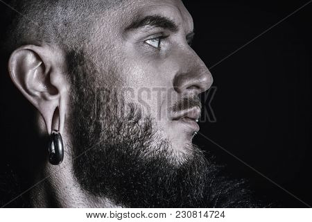 Close-up portrait of a bearded hipster man with piercing in the ears and lips. Studio shot over black background.