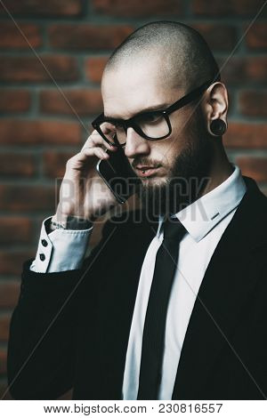 Close-up portrait of a businessman in elegant classic suit and piercing in the ears and lips talking on the phone. Men's beauty, fashion.