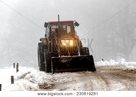 Drewsteignton, United Kingdom, 3rd March 2018:- A Tractor Clears Snow From A Roadway After The Beast