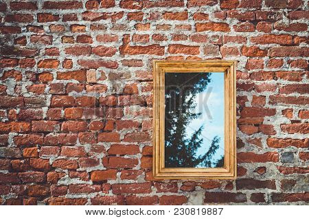 Ancient Brick Wall With Golden Frame Mirror Reflecting Trees With Sky On Background