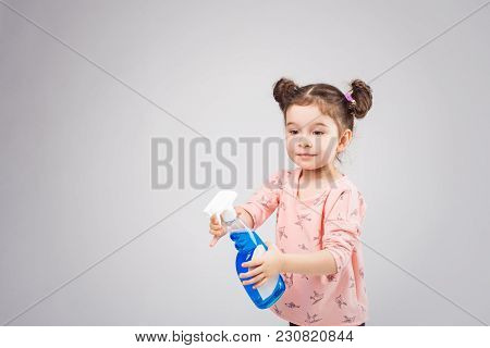 Little Girl Washes The Window. The Children Clean The House. Children Help At Home. Toddler Cleaning