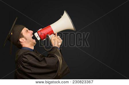 Graduate Man Shouting Into The Megaphone On Black Background