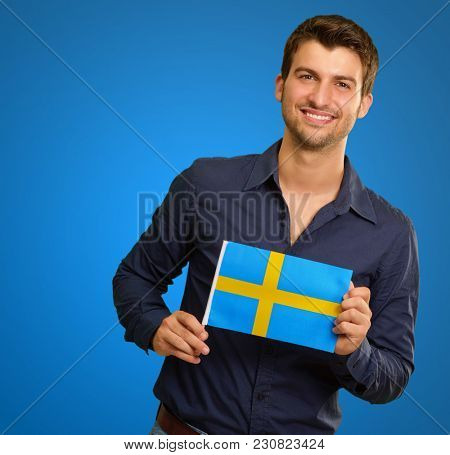 Young Happy Man Holding Sweden Flag On Blue Background