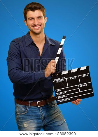 Happy Young Man Holding Clapboard On Blue Background