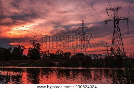 High-voltage  Power Lines At Sunset. Electricity Distribution Station. High Voltage Electric Transmi