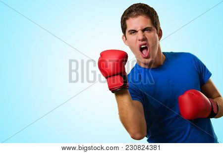 Aggressive Man Wearing Boxing Gloves against a blue background