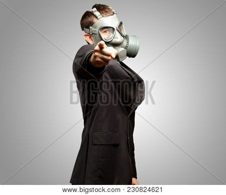Businessman Pointing With Gas Mask against a grey background