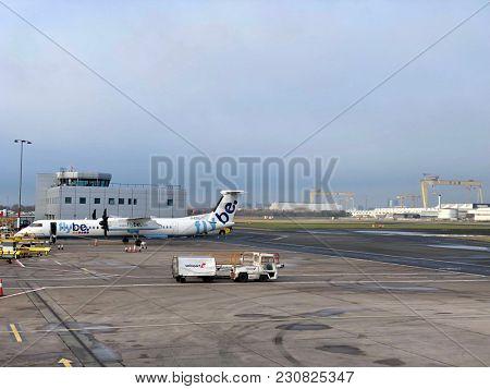 BELFAST, NORTHERN IRELAND - MARCH 12, 2018: A Flybe Bombardier Dash 8 Q400 passenger propeller plane parked at George Best Belfast City Airport in Belfast, County Antrim, Northern Ireland, UK.