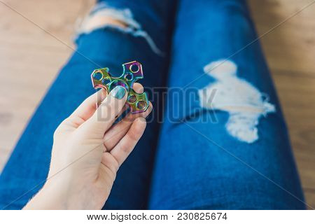 Girl Teenager In Holey Jeans Holds In Hands And Plays With Spinner.