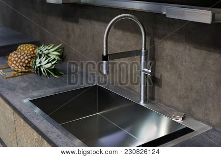 Stainless Steel Sink With A Tap On A Kitchen Counter.
