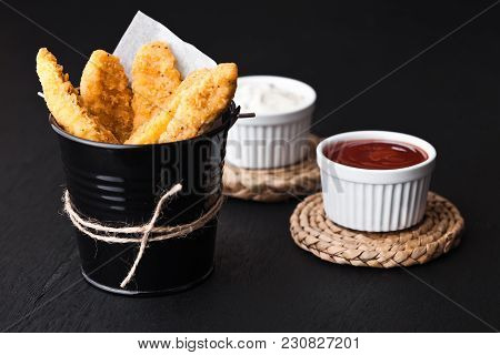 Fried Chicken Dippers In Black Bucket With Sauce On Black Background