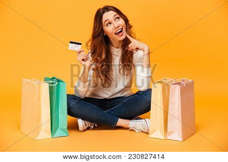 Pensive intrigued brunette woman in sweater sitting on the floor with packages while holding credit card and looking up over yellow background
