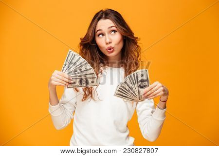 Pleased brunette woman in sweater holding money and waving them over yellow background