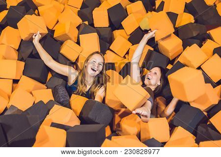 Two Young Women Having Fun With Soft Blocks At Indoor Children Playground In The Foam Rubber Pit In