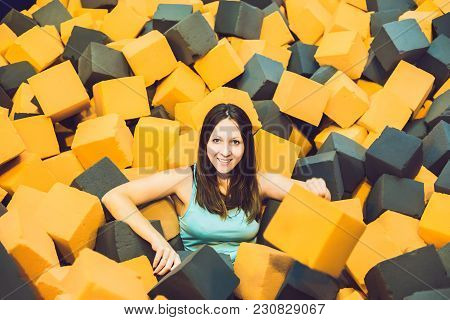 Young Woman Playing With Soft Blocks At Indoor Children Playground In The Foam Rubber Pit In The Tra