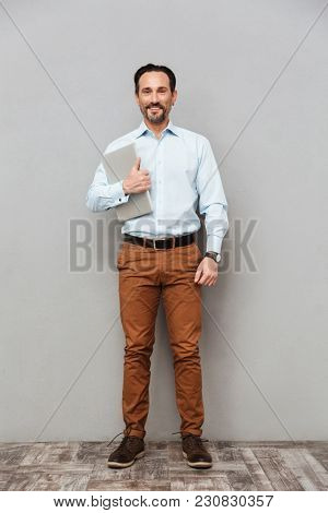 Full length portrait of a happy mature man dressed in shirt holding laptop computer while standing over gray background