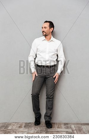 Full length portrait of a confident mature man dressed in shirt posing while standing over gray background