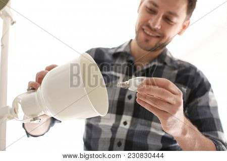 Man changing light bulb in lamp at home