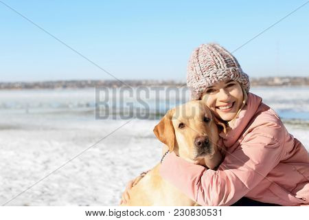 Portrait of woman hugging cute dog outdoors on winter day. Friendship between pet and owner