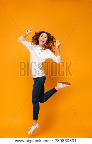 Full length image of Cheerful brunette woman in sweater jumping sideways while showing peace gestures and looking at the camera over yellow background
