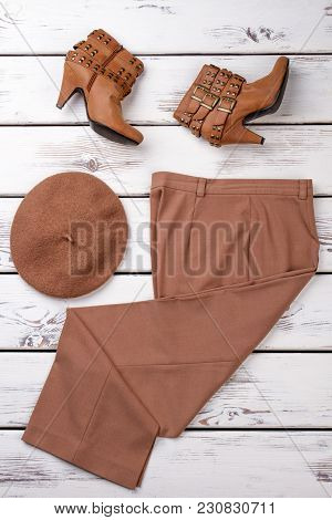 Set Of Brown Colored Women Clothes. Pair Of Brown Heel Shoes, Cap And Pants. Vertical View, Bright B