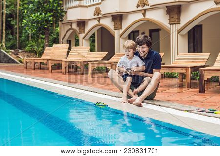 Father And Son Playing With A Remote Controlled Boat In The Pool.