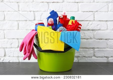 Bucket with cleaning supplies and tools on table near brick wall