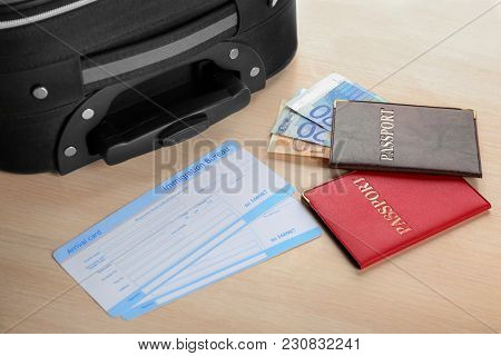 Passports, money and arrival cards on table near suitcase. Immigration reform