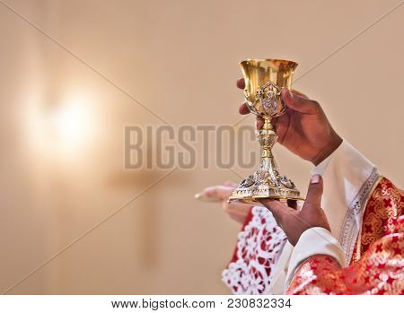 Hands Of The Priest Raise The Blood Of Christ