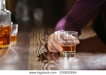 Man with glass of drink in bar, closeup. Alcoholism problem