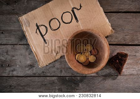 Coins and piece of cardboard with word POOR on wooden background