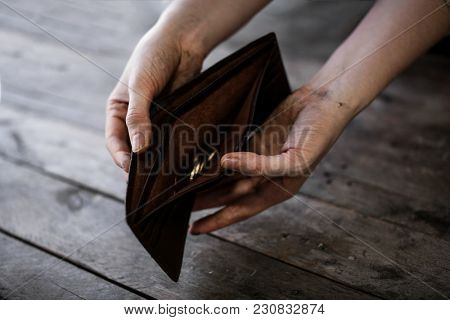 Poor woman holding purse with coins on wooden background