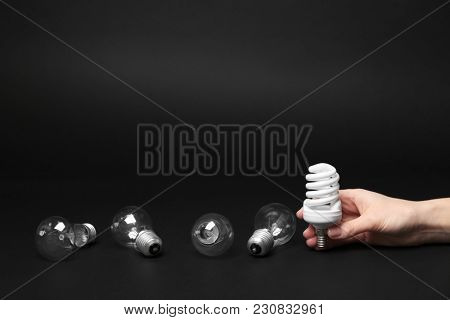 Woman holding fluorescent lamp near incandescent light bulbs on dark background
