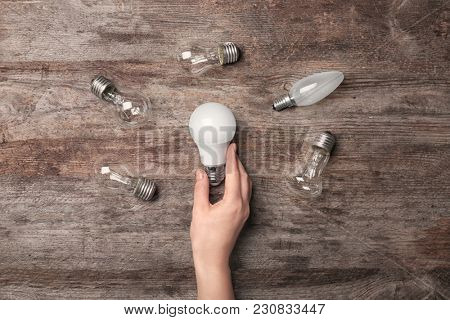 Woman holding LED lamp near incandescent light bulbs on wooden background
