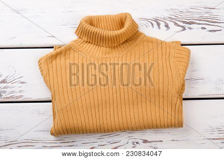 Yellow Folded Sweater. Pullover With Collar On Bright Wood Background.