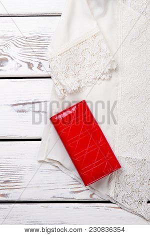 White Lace Blouse And Red Wallet, Close Up. Vertical Cropped View. Wooden Desks Surface Background.