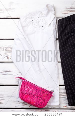 Pink Lace Purse On White Blouse. Vertical Cropped View. Wooden Desks Surface Background.