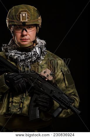 Photo of soldier in safety glasses with gun