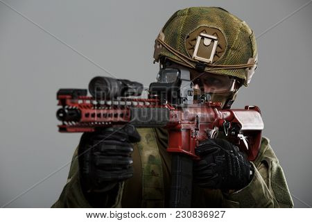 Photo of aiming military man in helmet with gun