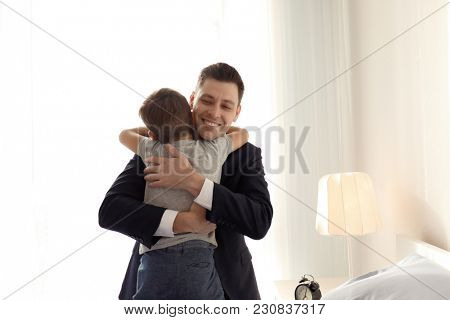 Father embracing son before leave for work in morning