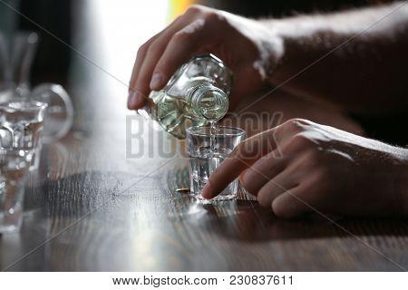 Man pouring drink into glass at bar, closeup. Alcoholism problem